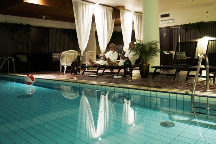 Par som sitter vid poolen